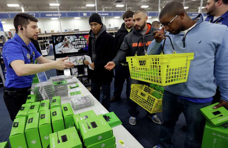 Nikolai Vacca, left, explains Xbox One accessories to customers at a Best Buy store on Friday, Nov. 22, 2013., in Evanston, Ill.  Microsoft is billing the Xbox One, which includes an updated Kinect motion sensor, as an all-in-one entertainment system rather than just a gaming console.  (AP Photo/Nam Y. Huh) Photo: Nam Y. Huh, Courtesy / AP