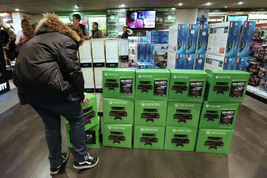 A man is about to buy the new XBox One game console on November 22, 2013 in Paris. Gamers in more than a dozen countries started snapping up new-generation Xbox One consoles Friday as Microsoft battled Sony to be at the heart of Internet age home entertainment. AFP PHOTO / Marion RuszniewskiMarion Ruszniewski/AFP/Getty Images Photo: MARION RUSZNIEWSKI, Courtesy / AFP