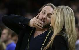 YouTube co-founder Chad Hurley, left, listens to a woman during the second half of an NBA basketball game between the Memphis Grizzlies and the Golden State Warriors Wednesday, Nov. 20, 2013, in Oakland, Calif. (AP Photo/Ben Margot)