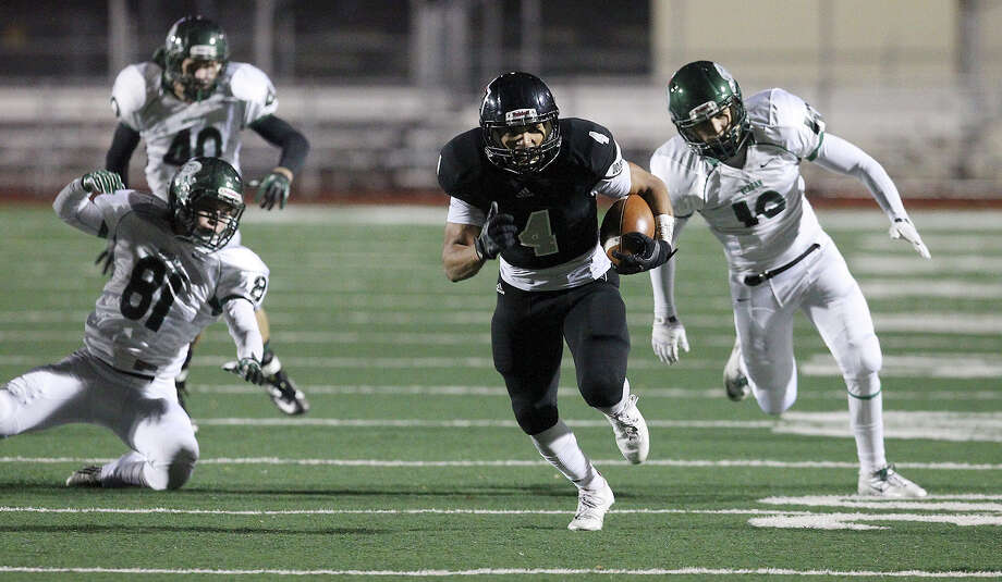 Steele's Justin Stockton (04) runs away from a trio of Reagan defenders to score a touchdown during their 5A playoff game at Comalander Stadium on Friday, Nov. 22, 2013. Photo: Kin Man Hui, San Antonio Express-News / ©2013 San Antonio Express-News