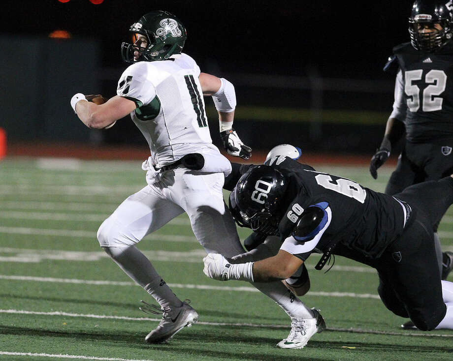 Reagan quarterback Ty Summers (11) gets wrapped up by Joshua Cavazos (60) during their 5A playoff game at Comalander Stadium on Friday, Nov. 22, 2013. Photo: Kin Man Hui, San Antonio Express-News / ©2013 San Antonio Express-News
