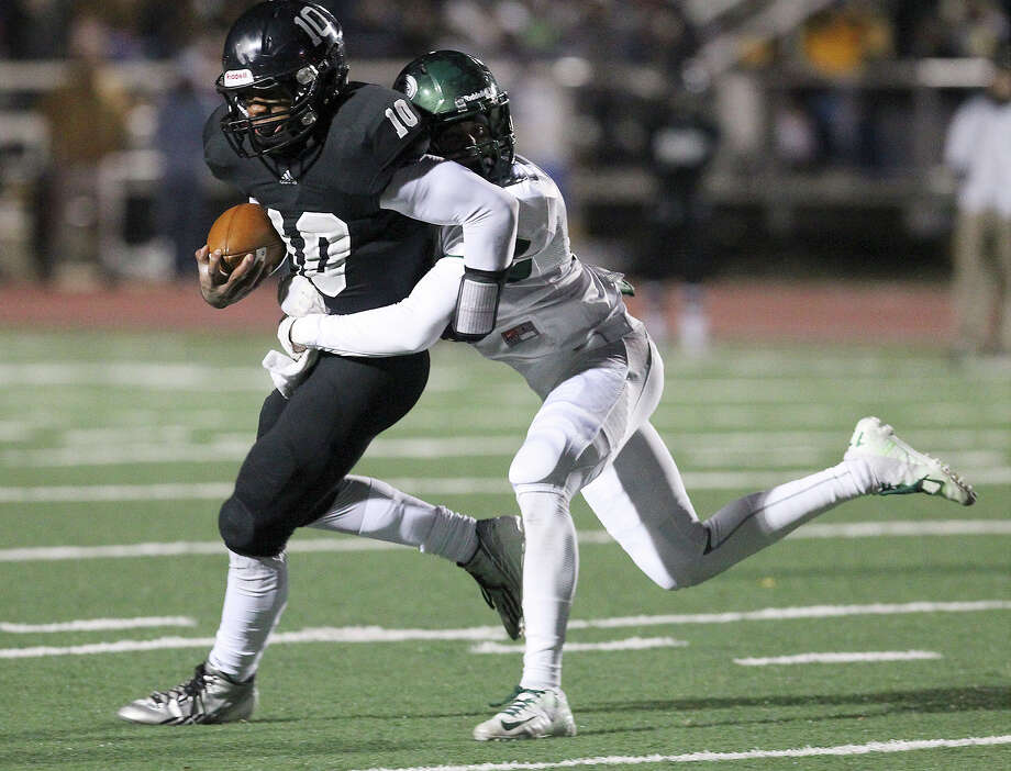 Steele's L.G. Williams (10) cannot shake off a tackle by Reagan's Efren Rodriguez (17) during their 5A playoff game at Comalander Stadium on Friday, Nov. 22, 2013. Photo: Kin Man Hui, San Antonio Express-News / ©2013 San Antonio Express-News