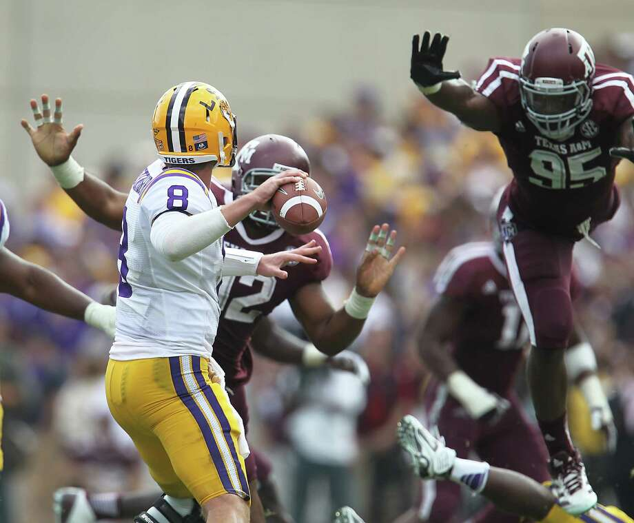 LSU quarterback Zach Mettenberger (8) will try to withstand pressure from Texas A&M's Julien Obioha, right, one of nine Aggies defenders from Louisiana. Photo: Karen Warren, MBI / Houston Chronicle