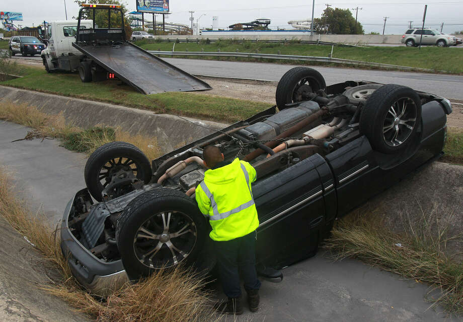 A wrecker operator prepares to upright a pickup that rolled into a culvert Friday morning in the 3500 block of the access road of Interstate 35 near Walters Street. Leroy Perez said he lost control while braking on the slick road. He was not injured. Photo: Photos By John Davenport / San Antonio Express-News