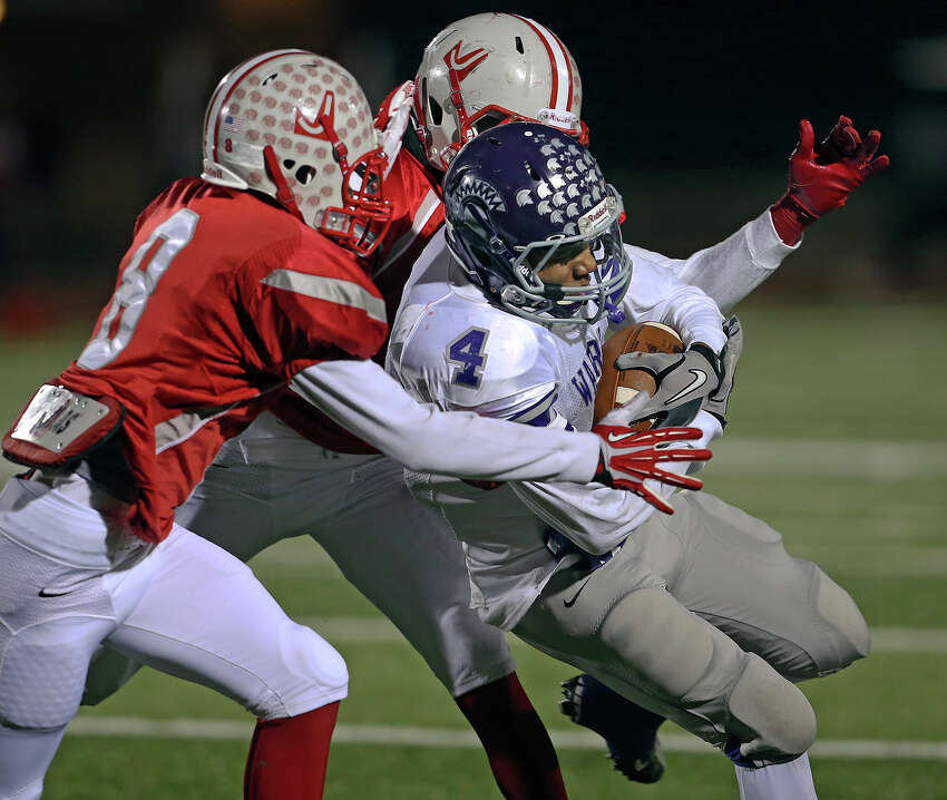 Warren's Aedric Robinson is brought down by Rocket defenders Cashon Grice (8) and Sean Eddington as Judson plays Warren in the second round of 5A football playoffs at Rutledge Stadium on November 22, 2013.