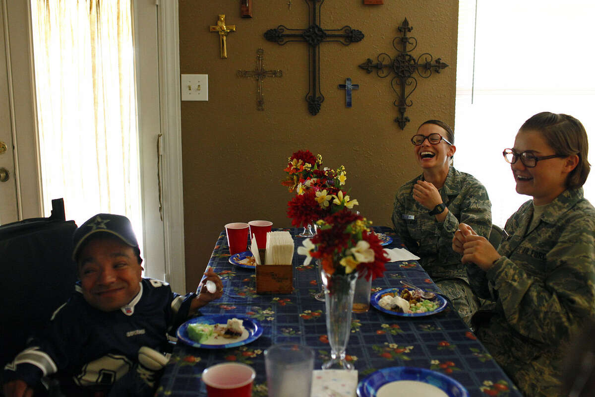 Every year, families take young military members like Kasha Creekmore and Megan Riney (right), who were then in basic training at Lackland AFB, into their homes for a Thanksgiving meal. This was the scene at the Ramirez home in 2010.