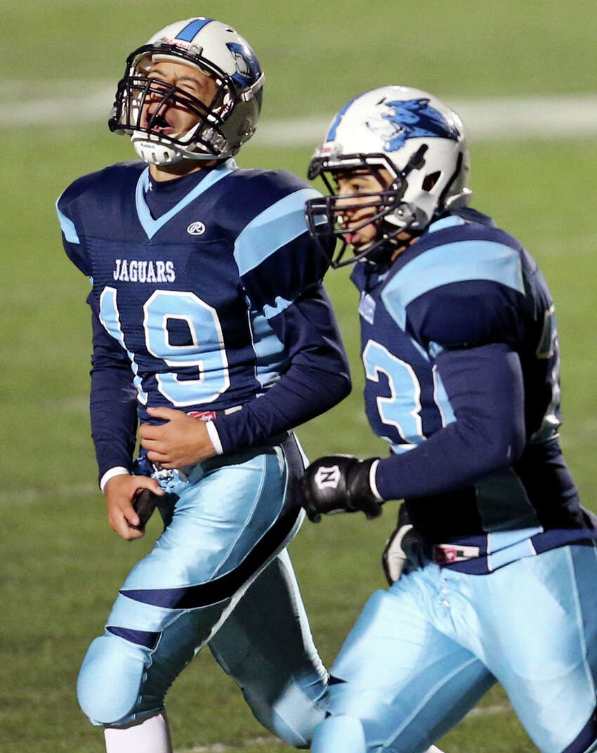 Johnson's Zachary Elder (left) celebrates as he walks off the field with teammate Nick Vidal after making a field goal late in second half action of their Class 5A Division II area playoff game against Brandeis Friday Nov. 22, 2013 at Heroes Stadium. Johnson won 23-17 in overtime.
