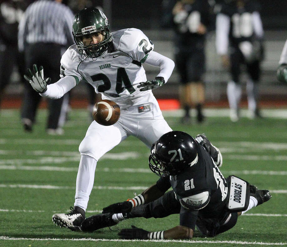 Steele's D'Angelo Wallace (21) misses a catch against Reagan's Eric Reyes (24) during their 5A playoff game at Comalander Stadium on Friday, Nov. 22, 2013. Photo: Kin Man Hui, San Antonio Express-News / ©2013 San Antonio Express-News
