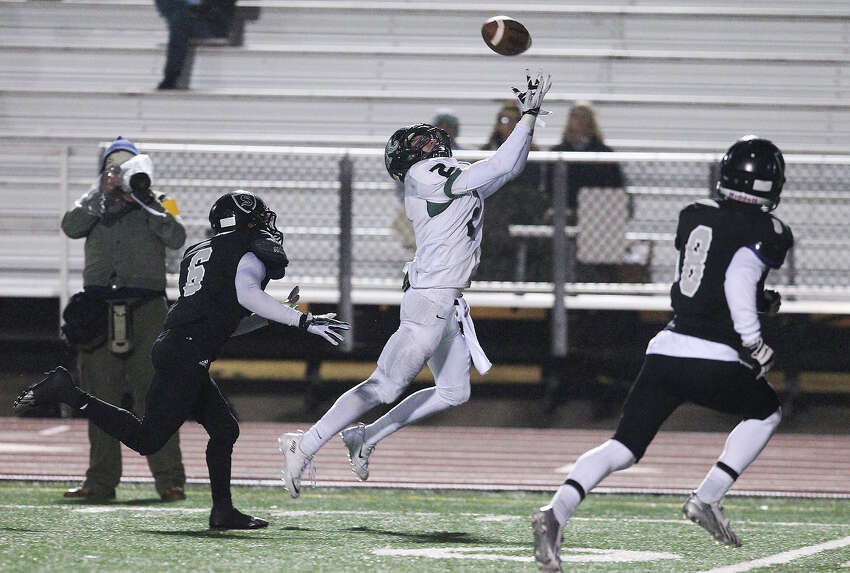 Reagan's Connor Heffron (02) reaches for a pass against Steele's Alvin Johnson (06) during their 5A playoff game at Comalander Stadium on Friday, Nov. 22, 2013.