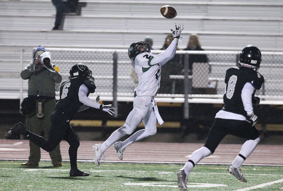 Reagan's Connor Heffron (02) reaches for a pass against Steele's Alvin Johnson (06) during their 5A playoff game at Comalander Stadium on Friday, Nov. 22, 2013. Photo: Kin Man Hui, San Antonio Express-News / ©2013 San Antonio Express-News