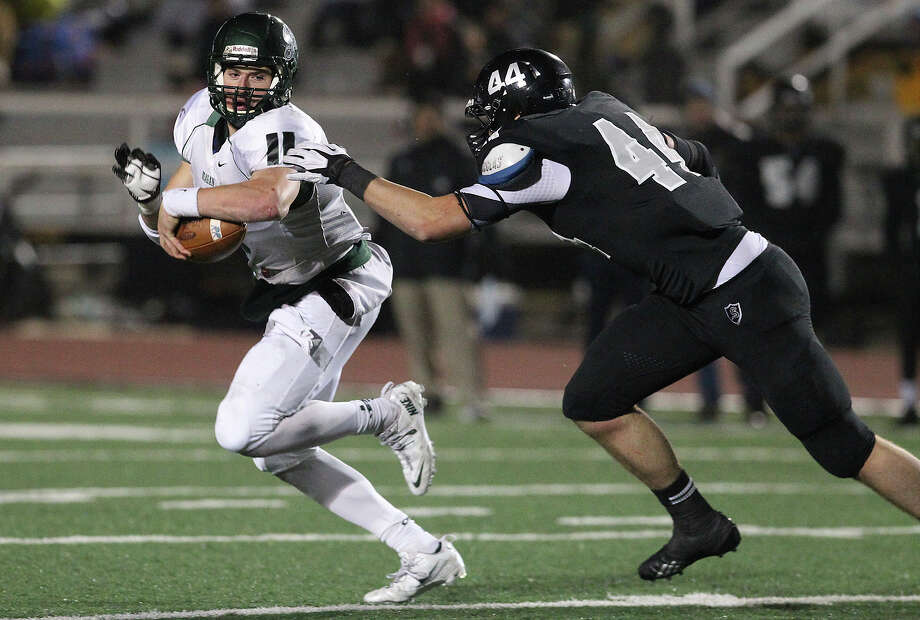 Reagan quarterback Ty Summers (11) runs from Steele's Josh Malin (44) during their 5A playoff game at Comalander Stadium on Friday, Nov. 22, 2013. Photo: Kin Man Hui, San Antonio Express-News / ©2013 San Antonio Express-News