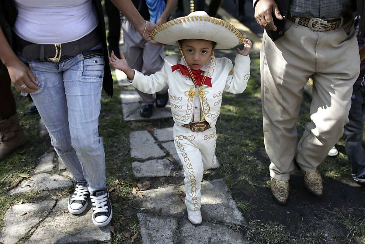Three-year-old Angel Tonoco wears a Mariachi suit during a pilgrimage in honor of Saint Cecilia, the Patron Saint of music, to the Basilica of the Virgin of Guadalupe in Mexico City, Friday, Nov. 22, 2013. Friday is Saint Cecilia's feast day. (AP Photo/Franklin Reyes)