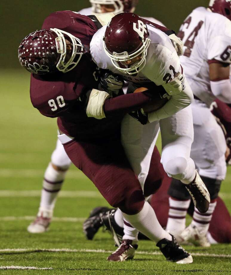 Cy-Fair's Ross Donnely (90) tackles Cinco Ranch's Jonathan Lugo (21) for a loss  during the first half of a high school football playoff game, Friday, November 22, 2013, at Pridgeon Stadium in Houston. Photo: Eric Christian Smith, For The Chronicle