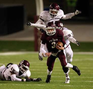 Cy-Fair's Clayton Kopecky (3) escapes the tackles of Cinco Ranch's Donovan Roberts (48), Justin Felske (45) and Tobi Ilesanmi (93) during the first half of a high school football playoff game, Friday, November 22, 2013, at Pridgeon Stadium in Houston. Photo: Eric Christian Smith, For The Chronicle
