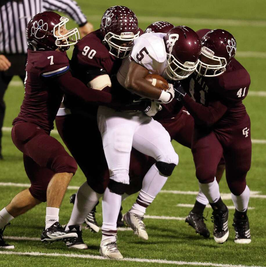 Cinco Ranch's Denzell Bates (5) is tackled for a loss by Cy-Fair's Pablo Salinas (7), Ross Donelly (92) and James Kohlschmist (41) during the first half of a high school football playoff game, Friday, November 22, 2013, at Pridgeon Stadium in Houston. Photo: Eric Christian Smith, For The Chronicle