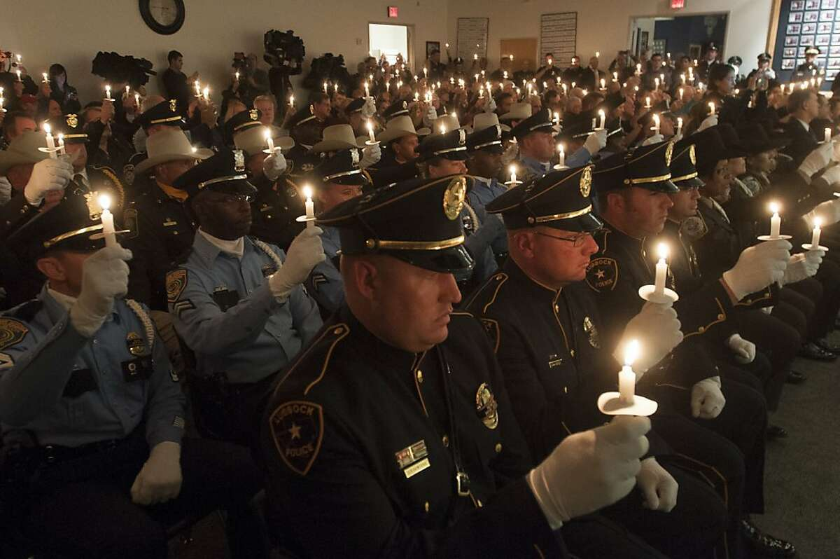 Police officers from throughout Texas hold candles during a ceremony commemorating slain Dallas Police Officer J.D. Tippit , who was killed by Lee Harvey Oswald. The event was held after the memorial for President Kennedy in Dallas Friday, Nov. 22, 2013. (AP Photo/Rex C. Curry)
