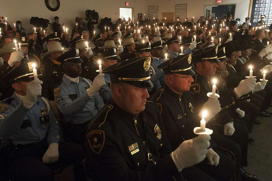 Police officers from throughout Texas hold candles during a ceremony commemorating slain Dallas Police Officer J.D. Tippit , who was killed by Lee Harvey Oswald. The event was held after the memorial for President Kennedy in Dallas Friday, Nov. 22, 2013. (AP Photo/Rex C. Curry) Photo: Rex C. Curry, Associated Press