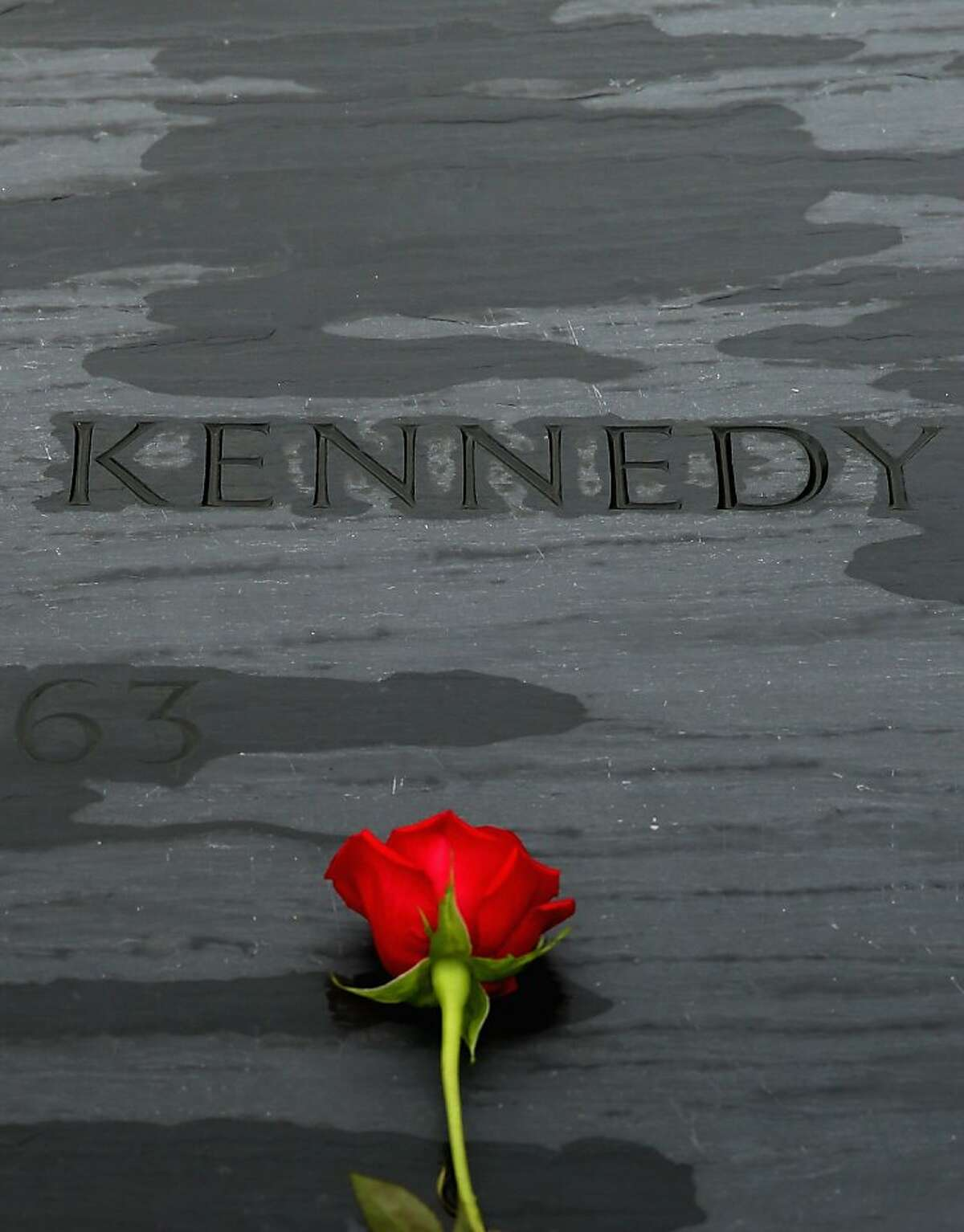 ARLINGTON, VA - NOVEMBER 22: A rose left by family members sits on top of former U.S. President John F. Kennedy's grave marker at Arlington National Cemetery November 22, 2013 in Arlington, Virginia. Remembrance ceremonies will be held arcoss the United States today, the 50th anniversary of the assisination of President Kennedy. (Photo by Chip Somodevilla/Getty Images)