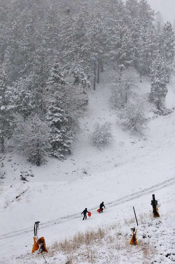 Jared Lesshana, bottom left, and Cody Handden, both from Azusa Pacific University in Azusa, hike up Mountain High Resort to get more speed on their sleds in Wrightwood, Calif, on Friday, Nov 22, 2013.  (AP Photo/The Victor Valley Daily Press, David Pardo) Photo: David Pardo, Associated Press