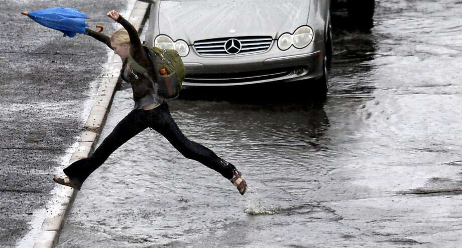 A woman leaps her way over the flooded gutters of a street near the University of Arizona in Tucson, Ariz., while coping with the after effects of heavy rains, Friday, Nov. 22, 2013. (AP Photo/Arizona Daily Star, Kelly Presnell)  ALL LOCAL TV OUT; PAC-12 OUT; MANDATORY CREDIT Photo: Kelly Presnell, Associated Press