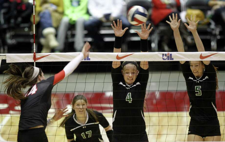 Churchill's Abby Buckingham (left) spikes the ball against a block attempt by Southlake Carroll's Megan Porter (4) and Timarie Nymeyer (5) during the Chargers' 5A semifinal victory. Photo: Mike Stone / For The Express-News