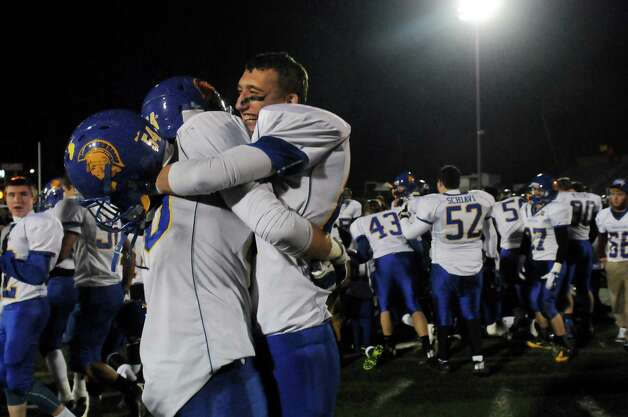 Queensbury's Keeghan O'Leary, center, embraces teammate Jeffrey Underhill after winning their Class A state semifinal football game 36-27 over Cornwall on Friday, Nov. 22, 2013, at Dietz Stadium in Kingston, N.Y. (Cindy Schultz / Times Union) Photo: Cindy Schultz / 00024745A