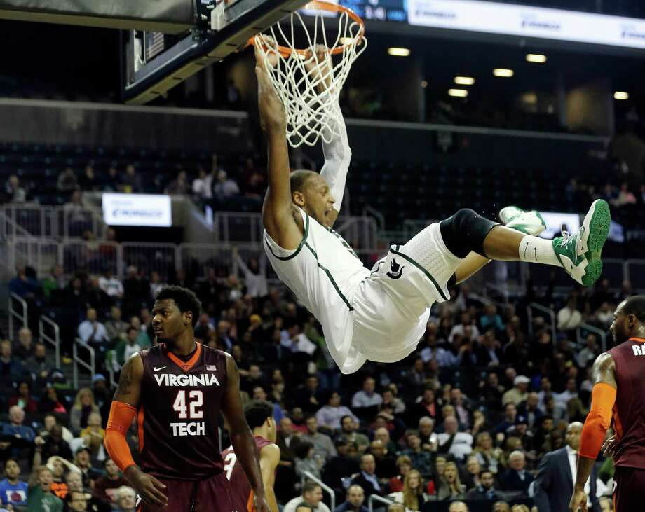 Michigan State's Adreian Payne (5) celebrates while hanging on the rim after dunking the basketball during the first half of a Coaches vs. Cancer NCAA college basketball game against the Virginia Tech, Friday, Nov. 22, 2013, in New York. (AP Photo/Frank Franklin II) ORG XMIT: NYFF120 Photo: Frank Franklin II / AP