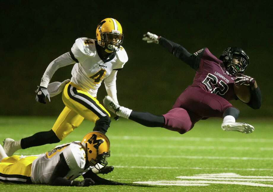George Ranch's Collins Kwabena, right, takes flight in pursuit of yardage after being upended by Fort Bend Marshall's Jordan Horace. Johntell Horton (4) also looks to get in on the action Friday at Mercer Stadium. Photo: Bob Levey, Photographer / ©2013 Bob Levey