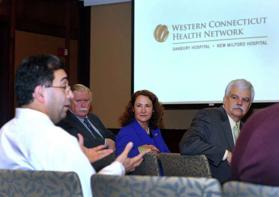 Dr. Ramin Ahmadi, left, talks about an announcement concerning expansion of the preventive medicine programs for the Western Connecticut Health Network, Friday, Nov. 22, 2013. Listening to him left are, James Maloney, president and CEO of the Connecticut Institute for Communities,  U.S. Rep. Elizabeth Esty and State Rep. Robert Godfrey. Photo: Carol Kaliff / The News-Times