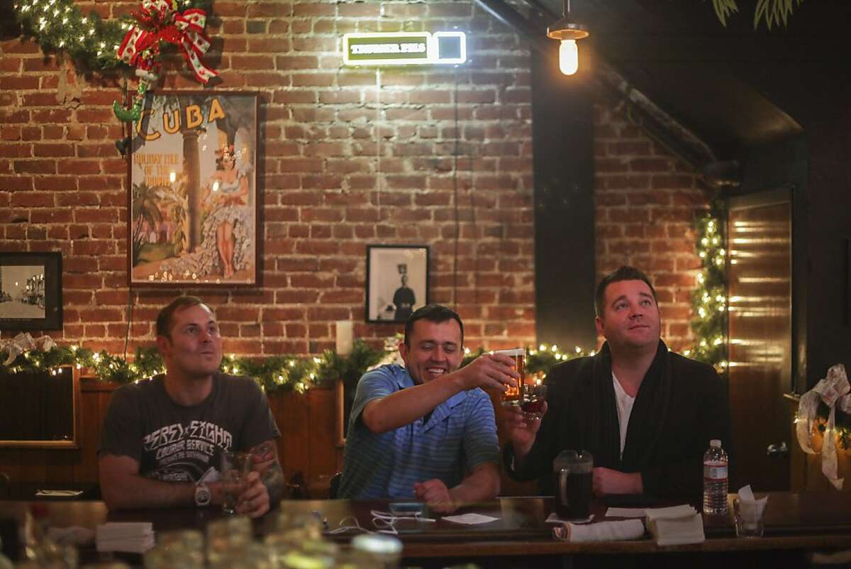 From left to right, Brandon Polk, Rodrigo Quintero and Jesus Bingham have a drink at the bar of Cha Cha Cha in San Francisco on November 22nd 2013.