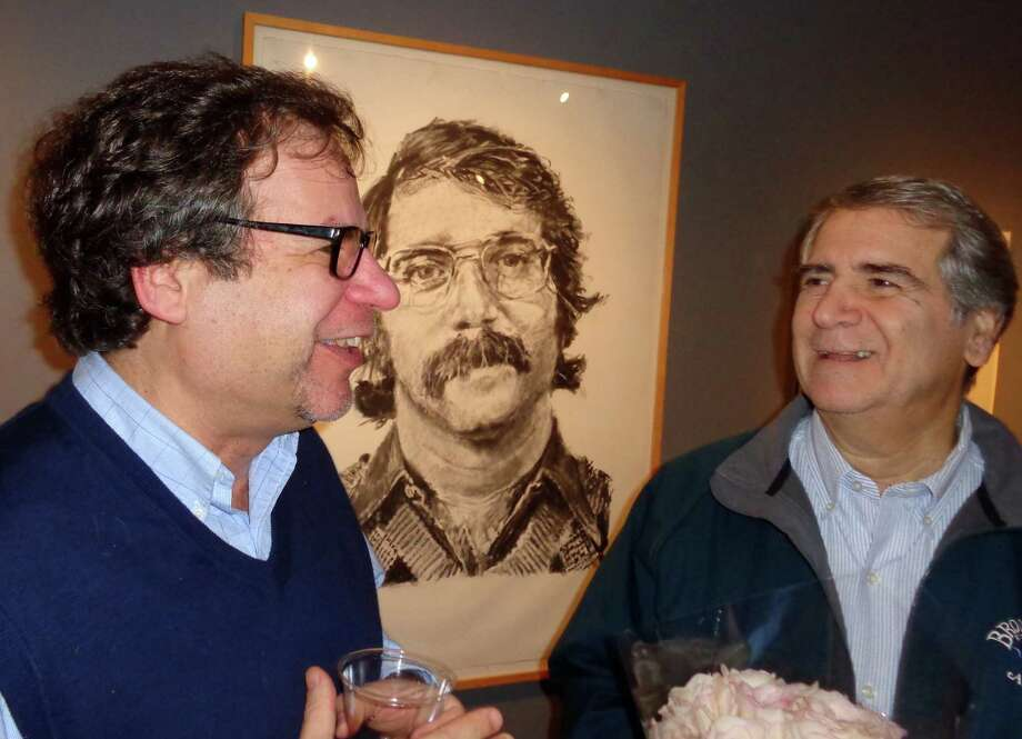"Yale art historian Jonathan Weinberg, left, who wrote the book ""Chuck Close Photo Maquettes,"" for an exhibit in New York, talks with Bob Elson of Westport at the Westport Arts Center during the opening reception for the exhibit, ""Chuck Close: About Face,"" which focuses on the photographic studies for the artist's celebrated potraits. The men are standing in front of a Close portrait of Elson, which the artist created in the early 1970s and gave to Elson and his wife Robin as a wedding present. Photo: Meg Barone / Westport News contributed"