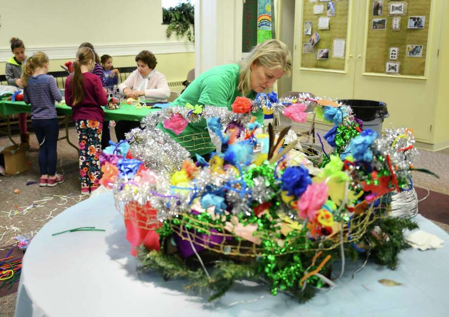 """Julie Dunn, a volunteer with Ben's Lighthouse, puts some finishing touches on a bird's nest, crafted by children, during Open Art Day, presented by Ben's Lighthouse and Emerald Sketch Art Therapy, at Trinity Church in Newtown, Conn. on Saturday, Nov. 23, 2013.  Children and parents of Newtown were invited to participate in the project to create sculptures and other works of art with a theme of """"safe places.""""  Works included a bird's nest, a lighthouse and a miniature community with paper streets and egg carton buildings. Photo: Tyler Sizemore / The News-Times"""