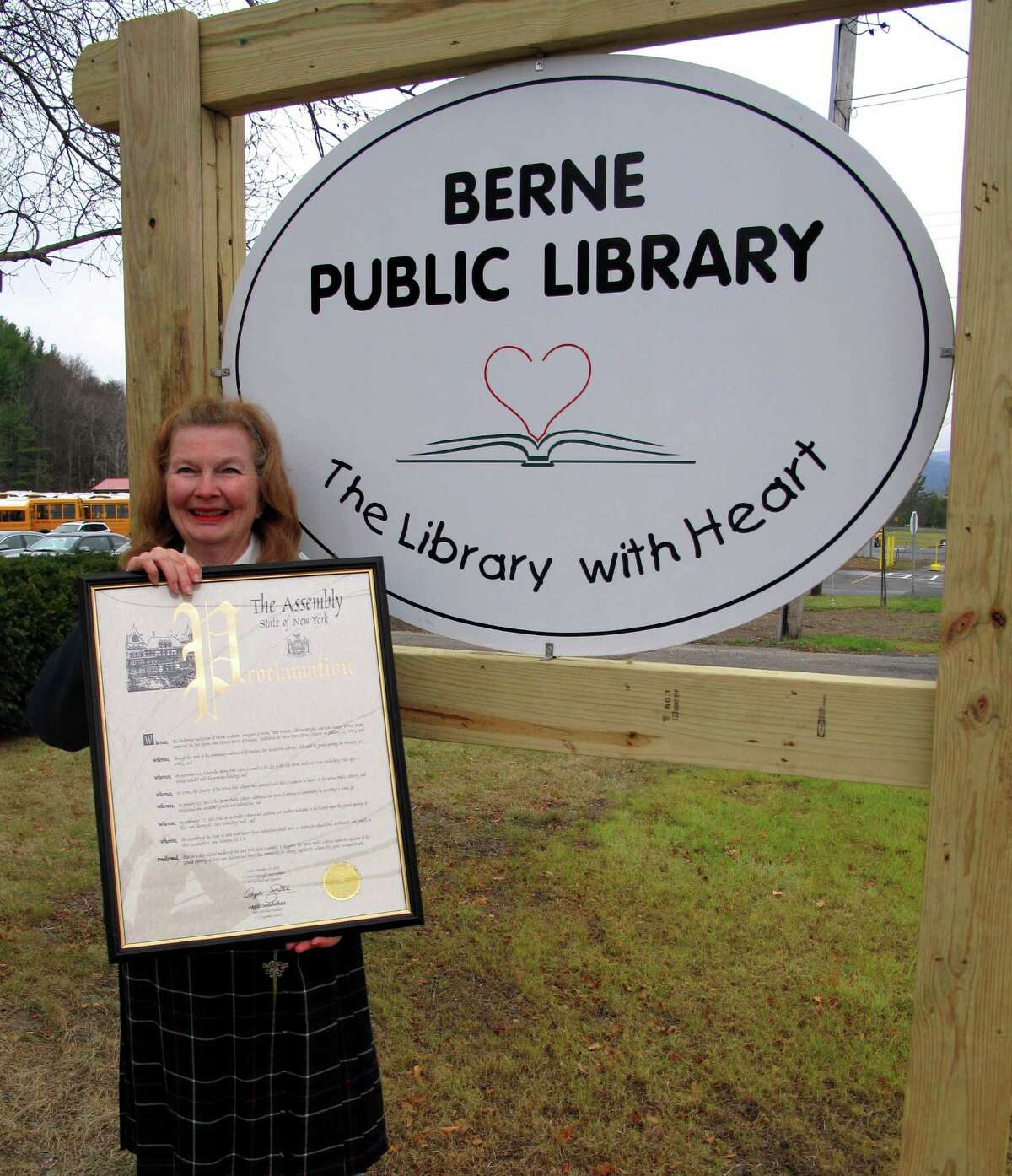 Mary Kinnaird, president of the library trustees, displays the state Assembly proclamation welcoming the new library in front of Berne Town Library's new sign. (Ron Barnell)