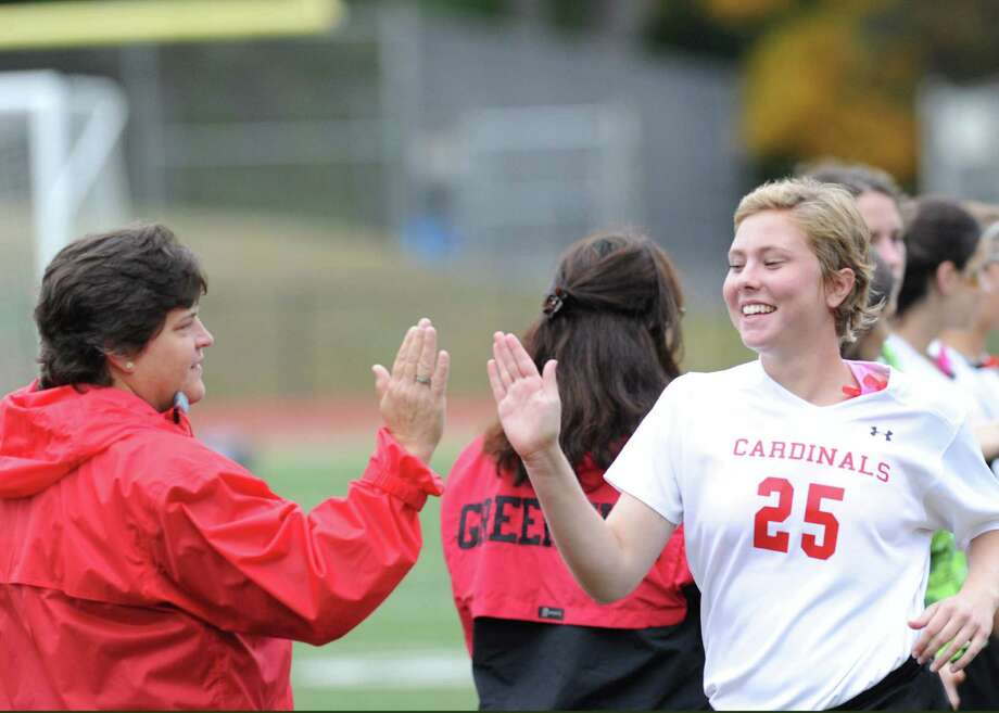 At left, Ally Orrico, Greenwich High field hockey coach, high-fives senior captain Nicole Graham (# 25) prior to the the match against Fairfield Ludlowe High School at Greenwich, Tuesday, Oct. 22, 2013. Graham was one of one of the seniors honored as part of senior day. Greenwich won the match over Fairfield Ludlowe, 4-1. Photo: Bob Luckey / Greenwich Time