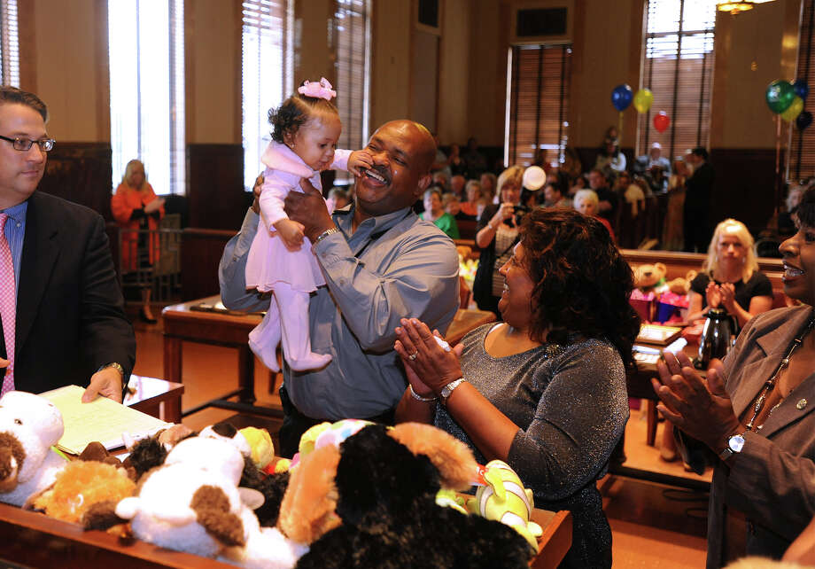 Deann Lucy, 8 months, reaches for Vincent Tyler's face during Adoption Day at the Jefferson County Courthouse on Friday. Along with 12 other families, Vincent and Lucy Tyler, right, were recognized by Judge Larry Thorne as new parents to adopted children.  Photo taken Friday, November 22, 2013 Guiseppe Barranco/@spotnewsshooter Photo: Guiseppe Barranco, Photo Editor