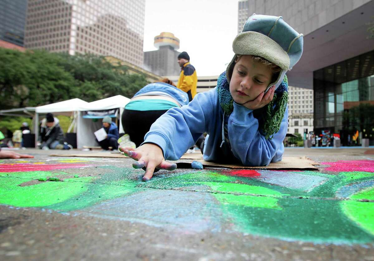 Katie Stensrud, 9, works on an art piece during Via Colori street painting festival in downtown Houston on Saturday, Nov. 23, 2013.