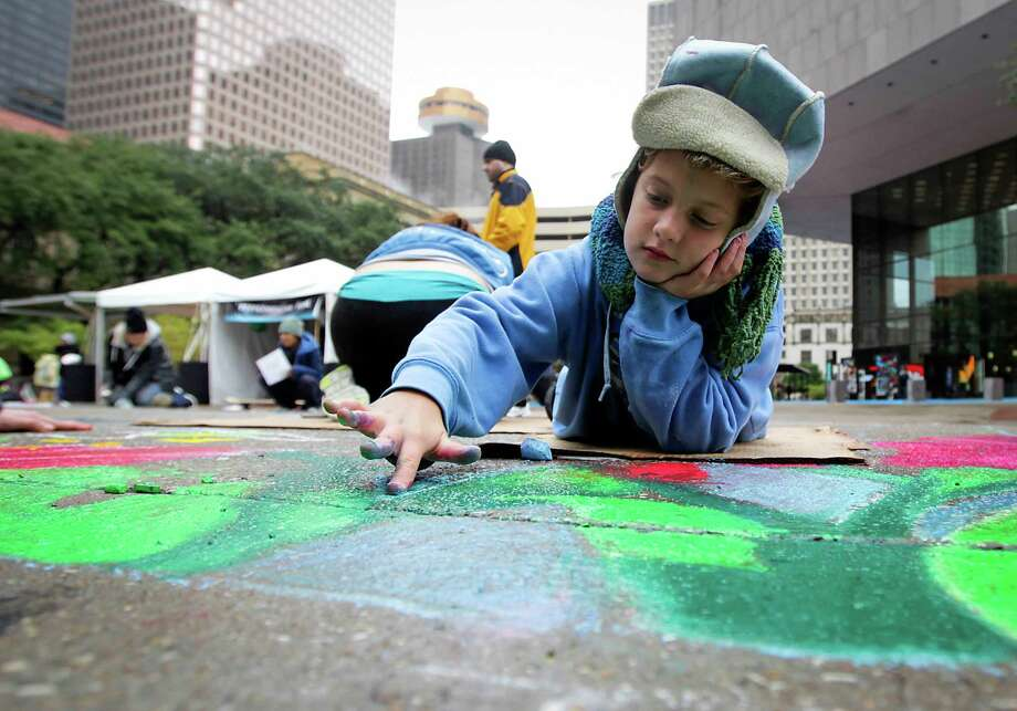 Katie Stensrud, 9, works on an art piece during Via Colori street painting festival in downtown Houston on Saturday, Nov. 23, 2013. Photo: James Nielsen, Houston Chronicle / © 2013  Houston Chronicle