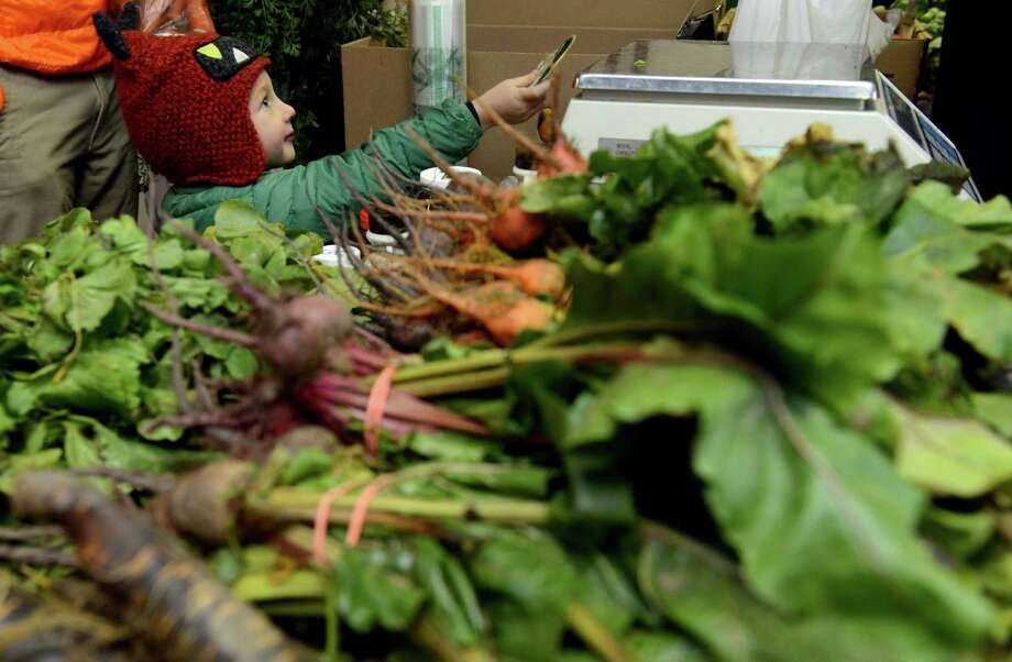 Four-year-old Charlie Gates, of Fairfield, pays for produce from Gazy Brothers Farm as he shops with his father for local ingredients for Thanksgiving dinner Saturday Nov. 23, 2013 at the Fairfield Winter Farmer's Market. Photo: Autumn Driscoll / Connecticut Post