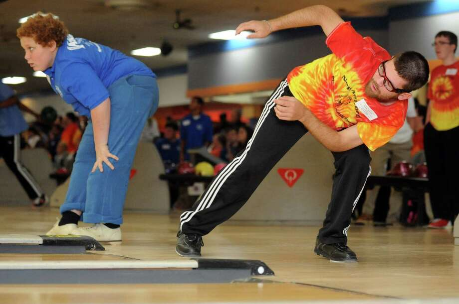 Timothy Schneider, 20, and Michael Gisondi, 11, both of Bethel, watch their balls strike the pins Saturday, Nov. 23, 2013 during the 2013 Holiday Sports Classic for Connecticut Special Olympics at AMF Lanes in Milford, Conn. Photo: Autumn Driscoll / Connecticut Post