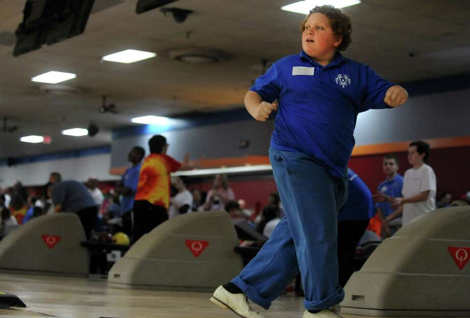Michael Gisondi, 11, of Bethel, watches his shot Saturday, Nov. 23, 2013 during the 2013 Holiday Sports Classic for Connecticut Special Olympics at AMF Lanes in Milford, Conn. Photo: Autumn Driscoll / Connecticut Post