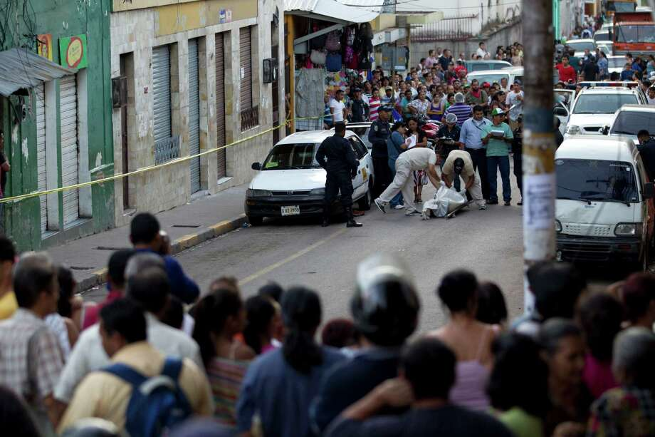 "Forensic workers cover the body of Benjamin Alvarez Moncada, 68, last week in downtown Tegucigalpa, Honduras. The taxi driver, known as ""Don Mincho,"" was gunned down as a warning from an extortion gang. Photo: Moises Castillo, STF / AP"