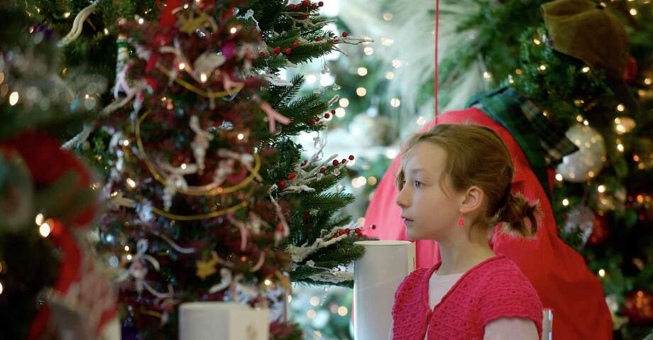 Maggie Leopold, 8, of Brookfield, is surrounded by trees at the Ann's Place Festival of Trees at the Matrix Conference & Banquet Center in Danbury, Conn. The event continues on Sunday,  10 am to 5 pm. Photo: H John Voorhees III / The News-Times Freelance