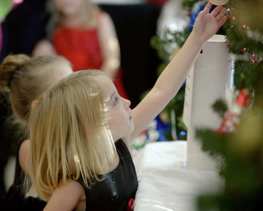Kaitlyn Biasetti, 4, of New Fairfield, looks at a tree at the Ann's Place Festival of Trees at the Matrix Conference & Banquet Center in Danbury, Conn, on Saturday, November 24, 2013 The event continues on Sunday,  10 am to 5 pm. Photo: H John Voorhees III / The News-Times Freelance