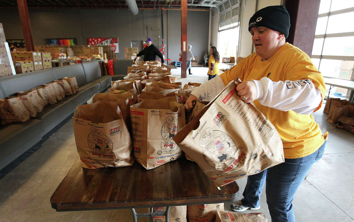 Civic engagement Rackspace's Tracy Gamez puts bags of food on a collection table to be donated during the Thanksgiving food drive partnered by Rackspace and the San Antonio Food Bank on Saturday, Nov. 23, 2013. Rackspace employees, Rackers, collected 1,500 boxes of food and frozen turkeys while the Food Bank kicked in other items for over 1,100 families according to officials. Rackers along with Roosevelt High School and area community volunteers all pitched in to help at the event.