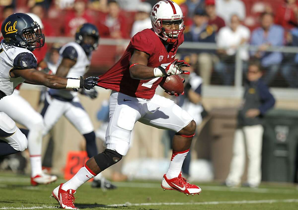 Stanford's TY Montgomery, (7) stretches a first quarter catch into a touchdown despite being pursued by Cal's Cameron Walker (14), as the Stanford Cardinal takes on the California Golden Bears in the 116th Big game match up on Saturday Nov. 23, 2013 at Stanford stadium in Palo Alto, Ca.