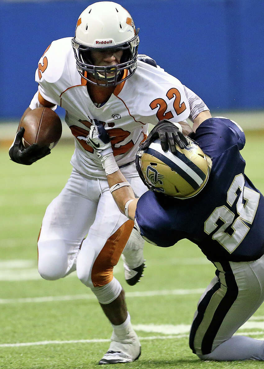 Maverick running back DJ Smith pushes through Peyton Dees as Madison plays O'Connor in second round 5A football playoffs at the Alamodome on November 23, 2013.