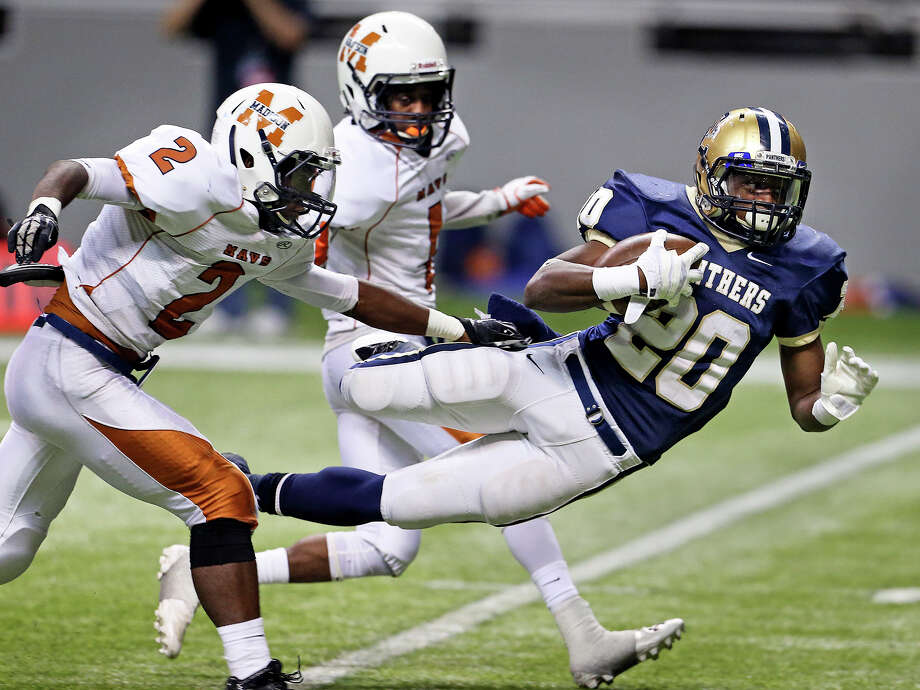 Panther running back Jamontae Foster gets some extra yards on a lunge past Latrell Sledge (2)  toward the goal as Madison plays O'Connor in second round 5A football playoffs at the Alamodome on November 23, 2013. Photo: TOM REEL