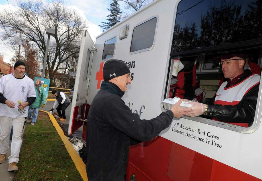 Chris Marotta, center, of Glenville, a taper volunteering with District Council No. 9 to work on a damaged home, get a turkey dinner from American Red Cross volunteer Jim Morrill on Saturday Nov. 23, 2013 in Fort Plain, N.Y. (Michael P. Farrell/Times Union) Photo: Michael P. Farrell / 00024741A