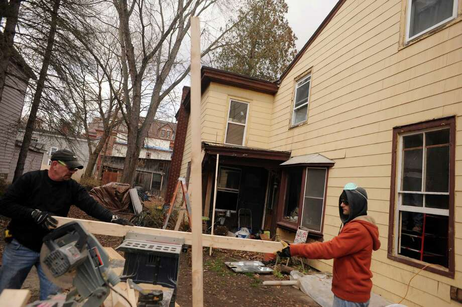 Paul Brennan, left, and his son Raymond Brennan, volunteers with District Council No. 9 , work on a  damaged home on Saturday Nov. 23, 2013 in Fort Plain, N.Y. (Michael P. Farrell/Times Union) Photo: Michael P. Farrell / 00024741A