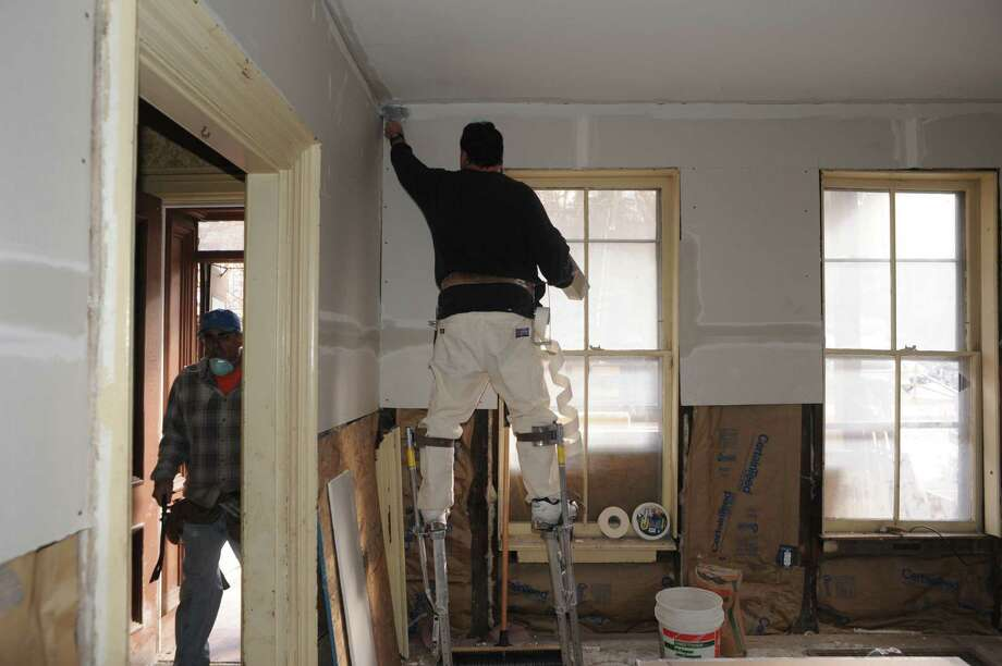 Taper Joe Willis, center, volunteers with District Council No. 9 , to work on a damaged home on Saturday Nov. 23, 2013 in Fort Plain, N.Y. (Michael P. Farrell/Times Union) Photo: Michael P. Farrell / 00024741A